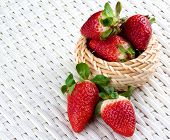Heap Of Big Ripe Strawberries In Wicker Bowl Closeup On White Wicker Background poster