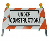 A road barricade reads Under Construction as it blocks the way and keeps you from moving forward, as