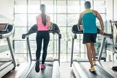 Full length rear view of a fit woman and her cardio workout, partner running on treadmills side by s poster