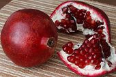 One Whole Ripe Pomegranate Fruit Lies Next To The Slices Of Pomegranate. Bright Ripe Red Pomegranate poster