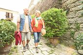 Happy Senior Couple Walking Holding Hand In San Marino Old Town Castle - Active Elderly And Travel L poster