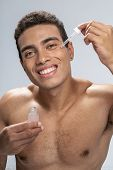 Cheerful Young Male Rejuvenating His Around Eyes Area poster