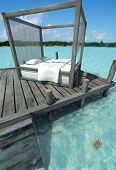 Canopy bed on a pier on a Caribbean landscape