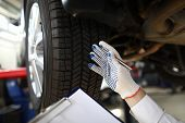 Focus On Specialist Male Hand Wearing White Glove And Inspecting Tires Of Modern High-tech Sporting  poster