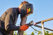 Worker Welder Working Welding Steel In Industry With Safety Mask Safety Gloves And Safety Equipment. poster