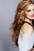 smiling beautiful woman with long curly blond hair wearing bright pink lipstick and smoky eyeshadow on studio background.