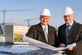 Male developers with blueprints at  construction site discuss architect project