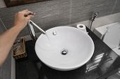 Male Hand Use A Faucet In A Bathroom Interior With White Round Sink And Chrome Faucet. Water Flowing poster