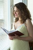 schwangere Frau in der Nähe von Fenster
