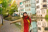 Beautiful Woman With Hands Outstretched On Street Of Strasbourg. Vacations Lifestyle. Woman Expressi poster