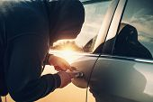 Car Robber Or Thief Trying To Break Auto Door Lock, Close Up. Car Theft Concept. poster
