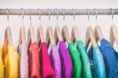 Clothes hanging on clothing rack wardrobe fashion apparel selection of rainbow color t-shirts on clo poster