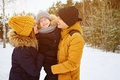 Portrait Of Happy Family In Winter Day. Mom And Dad Are Cuddling And Kissing Their Little Son In Win poster