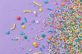Sprinkles On Purple Background - Cake Topping Sprinkles Sprayed On Lilac Background - Top View poster