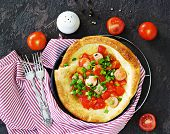 Dutch Baby Pancake Filled Tomatoes, Sausages And Cheese In A Serving Cast-iron Frying Pan On A Dark  poster