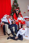 Christmas Family. Family Celebration. Smart Family Next To The Christmas Tree. Large Large Family As poster