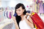 Asian Woman With Shopping Bag And A Credit Card