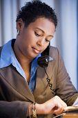 African businesswoman checking watch