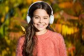 Educational And Downloadable Audio Books For Children. Kid Girl Relaxing Near Autumn Tree With Headp poster