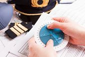Close up of an airplane pilot hands with holding pattern calculator with equipment including hat, ep