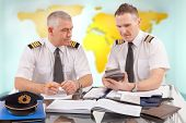 Two airline pilots preparing to flight, checking calculator, papers, flight plan, log book. Pilots are sitting in AIS ARO Air Traffic Services Reporting Office