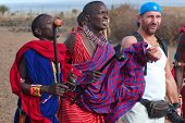African men from Masai tribe dance with a tourist