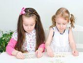 Dos niñas jugando Domino en la mesa