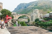 MOSTAR, BOSNIA - AUGUST 9: Tourists on the old bridge  on August 9, 2012 in Mostar, Bosnia. The old bridge is a reconstruction of a 16th century Ottoman bridge in the city of Mostar.
