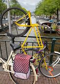 pic of houseboats  - A bicycle parked vertically on a bridge with Amsterdam The Netherlands canal and houseboats in background - JPG