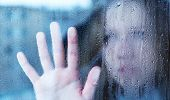 stock photo of raindrops  - hand of young woman melancholy and sad at the window in the rain - JPG