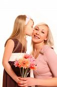 Little Girl With Flowers Kisses Her Mother On A White Background