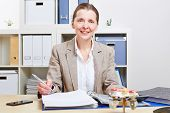 Happy elderly business woman sitting with files in her office