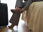 Tired Business Woman Taking Shoes Off In Hotel Room After Trip