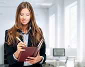 Businesswoman writing notes on her agenda
