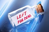 "An artistic stress concept of a vintage bottle with a message ""left for dead"""