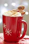 stock photo of ginger man  - Gingerbread cookie men in a hot cup of cappuccino - JPG