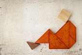 abstract sitting or relaxing figure built from seven tangram wooden pieces, a traditional Chinese pu