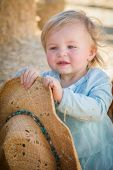 foto of baby cowboy  - Adorable Baby Girl with Cowboy Hat in a Country Rustic Setting at the Pumpkin Patch - JPG