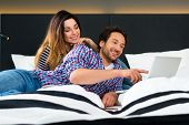 Young Couple lying in the bed of a hotel room, they are on vacation and using the wifi in the room f