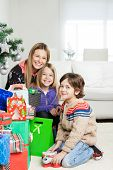 Portrait of happy mother and children with gifts sitting at home during Christmas