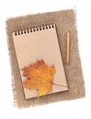 Brown paper notepad with pencil and autumn leaf over burlap. Isolated on white background