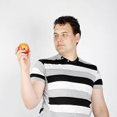 Brunet Handsome Man Holds Apple And Looks At It On White Background.