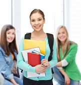 education, youth, school, teamwork concept - smiling student with books and schoolbag