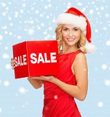 shopping, gifts, christmas, x-mas concept - smiling woman in santa helper hat with red sale sign