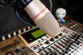 stock photo of recording studio  - Studio recording microphone with sound control panel and disco ball over music CDS - JPG
