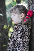 stock photo of overcoats  - Pretty little girl with pink bows in overcoat looks away in forest - JPG