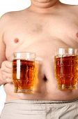 stock photo of beer-belly  - Color photo of a large belly and a mug of beer - JPG
