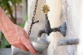 Man taking potable water in a street side tap
