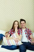 Portrait of young couple during watching TV