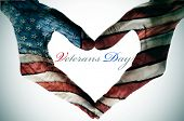 veterans day written in the blank space of a heart sign made with the hands patterned with the colors and the stars of the United States flag
